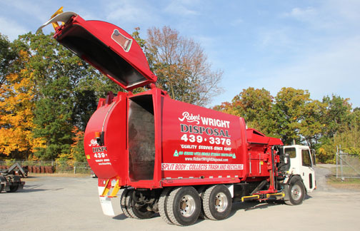 Red garbage truck with half of back end open