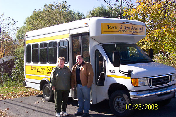 Susan Kidder and John Crisalli standing next to small bus